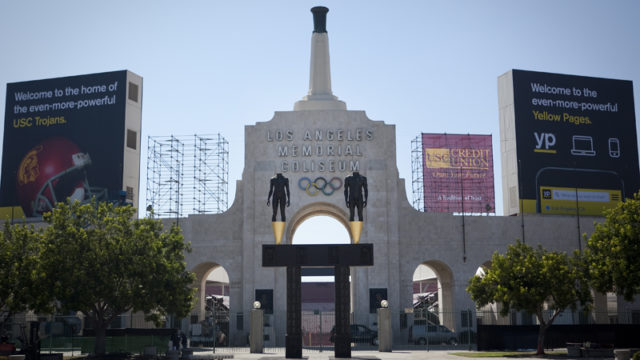 A view of the main entrance of the LA Coliseum with statues and an unlit olympic torch cauldron.