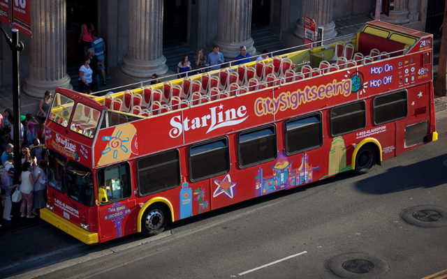 Starline tour bus with double-decker open top seats parked on a street in Hollywood.