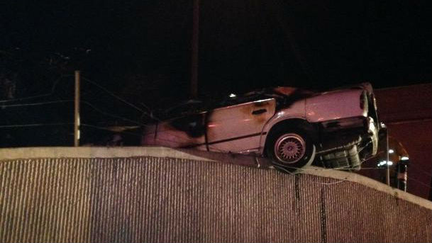 The wrecked, early-model BMW rests on the edge of a freeway embankment. Photo courtesy Orange County Fire Authority