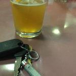 a half-full beer glass and car keys sitting on a bar