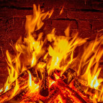 A residential fireplace burns wood.