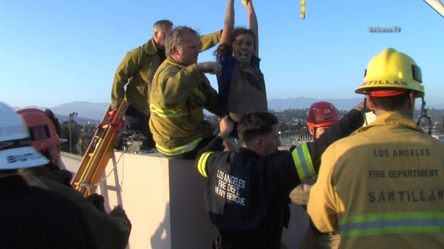 Firefighters pull the unidentified woman to safety. Courtesy OnScene.TV