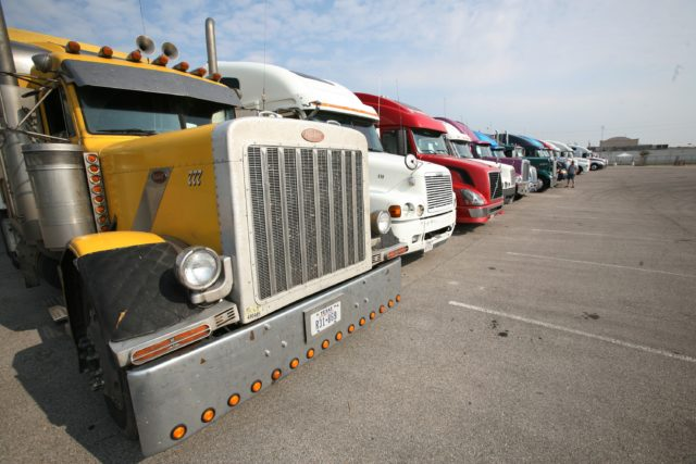 a row of big rig trucks parked in a large lot.