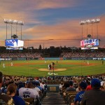 a dodger stadium view of the field from seats behind home plate, showing the field, players, and fans in their seats, along with a batter in the box.