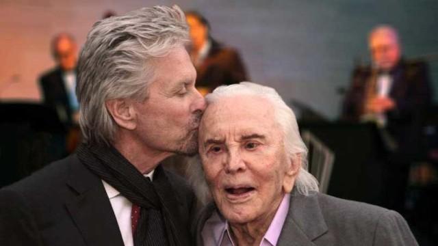 Michael Douglas kisses his dad, Kirk, on his 99th birthday. Photo via Facebook