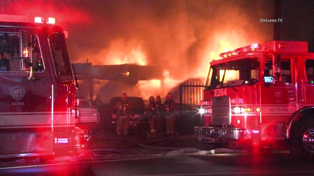 An auto body shop and 15 vehicles on the property were damaged in a greater-alarm fire in South Los Angeles, authorities said. Photo via OnScene,TV.