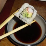 A sushi roll and a bowl of soy sauce. Photo via Pixabay.