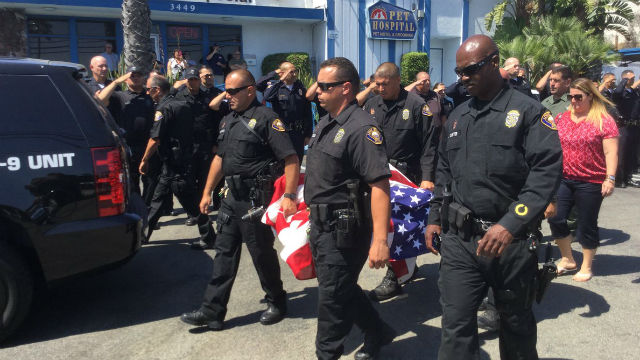 Officers pay their respects to fallen K-9 Credo as he is carried from the hospital by K-9 officers. Courtesy Long Beach Police