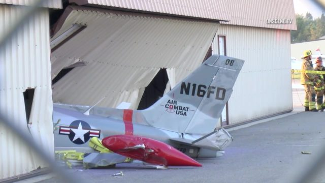 The tail of the crashed plane extends from the hanger in Fullerton. Courtesy OnScene.TV