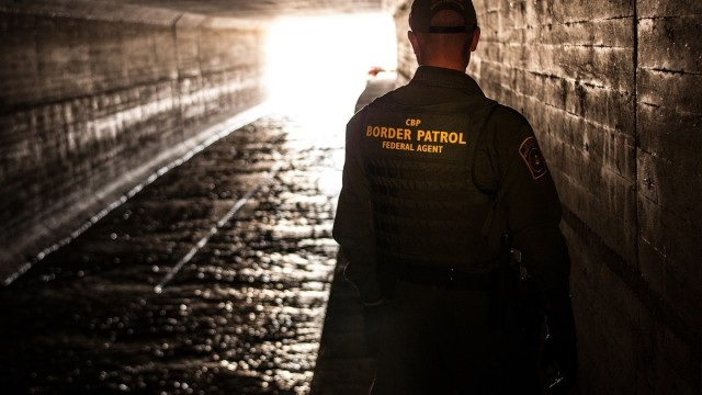 A Border Patrol agent looks out a water drain tunnel that runs from Mexico Photo by Josh Denmark/CPB