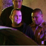 Harry Burkhart (second from left) being detained by law enforcement personnel. Photo via OnScene.TV
