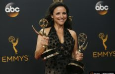 Julia Louis-Dreyfus poses with an Emmy Award trophy in each hand.