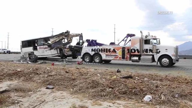 The remains of a tremendously damaged tour bus are towed away from the scene of a fatal big rig collision that killed 13 people and injured 31 others. Courtesy OnScene.TV