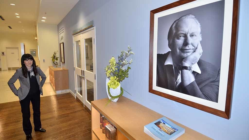 Scientology spokeswoman Erin Banks with photo of founder L Ron Hubbard, who lived in San Diego at different stages of his life. Photo by Ken Stone