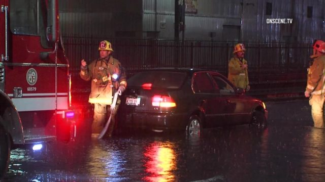 Los Angeles Fire Department personnel prepare to tow a flooded car at  Long Beach Avenue and East 50th Street. Courtesy OnScene.TV
