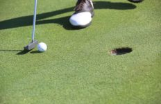 a golfer's feet with club and golf ball near a hole on the course.