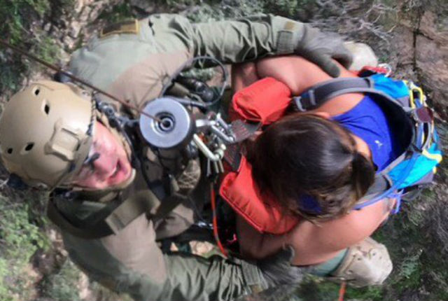 A sheriff's deputy holds the injured woman as the helicopter lifts off. Courtesy Los Angeles County Sheriff