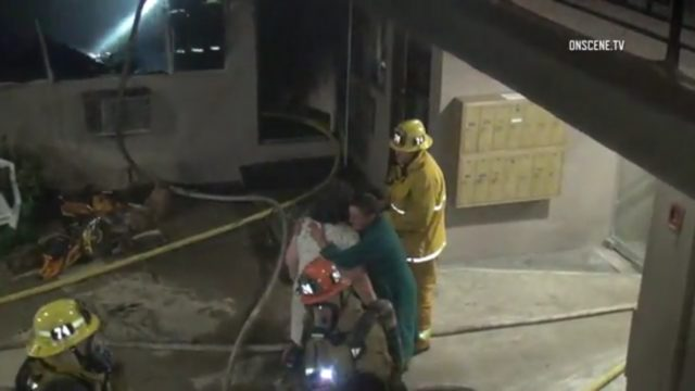 As residents look on, fire crews work to extinguish an apartment house blaze in Tujunga that killed one man. Photo: OnSceneTV