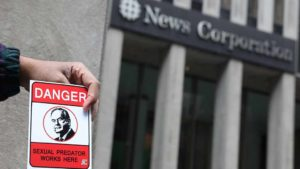 A man, who said he was hired, displays fliers opposing Fox News Channel TV anchor Bill O'Reilly outside the News Corporation headquarters in New York City, in New York, U.S. April 19, 2017. Photo by Shannon Stapleton via Reuters