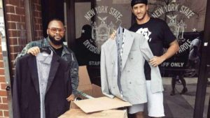Colin Kaepernick (right) helps hand out system suits in Queens, New York. Photo via Twitter