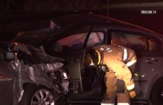 Firefighter examines wrecked vehicle