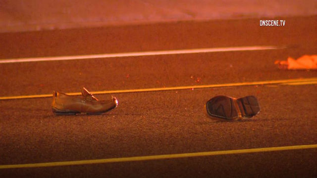 the shoes of the victim hit and killed by two vehicles in Athens, lie in the road illuminated by streetlamps and emergency vehicle lights.