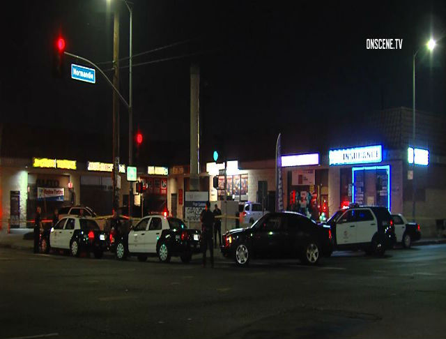 police and squad cars surround a corner strip mall at normandie avenue at night where a man was shot dead
