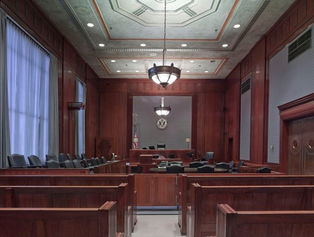 An empty courtroom with benches, judges bench flag and elaborate chandelier.