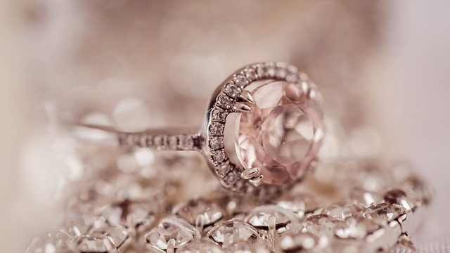 Close-up photo of many loosea diamond stones and a diamond ring .
