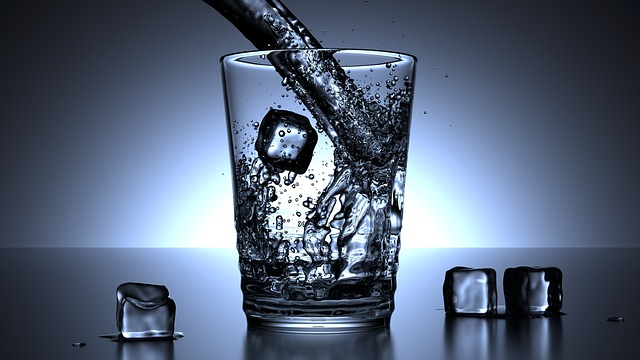 Drinking water in a glass with ice cubes.