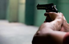Close-up photo of a person aiming a gun and preparing to shoot.