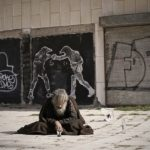 a homeless man sits on the street with graffiti covered buildings behind him.