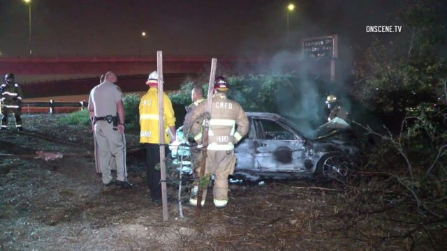 a smoldering car on the 55 Costa Mesa freeway is surrounded by emergency personnel
