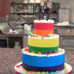 A custom cake created for a divorce celebration depicts a tuxedo-wearing groom kicking another off of the top of a multi-tiered cake decorated in the colors of gay pride.