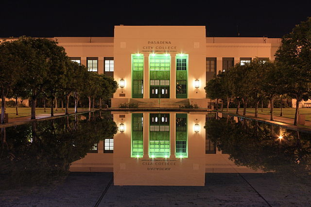 An art deco styled building and a reflecting pool at night on the campus of Pasadena City College.