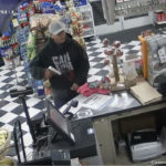 A Santa Ana gas station robbery suspect pulls a gun from his sweatshirt.