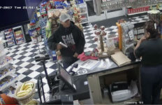 A Santa Ana gas station robbery suspect pulls a gun from his sweatshirt.