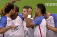 Members of the US Soccer Team congratulate each other on the field after a goal has been scored.