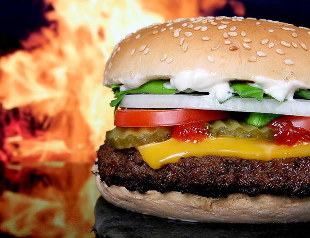 a restaurant hamburger sits on a table in front of a roaring fireplace.