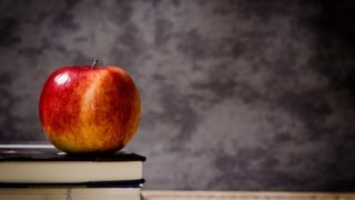 Schoolbooks and an apple sit on a desk.