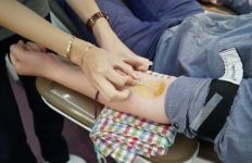 A blood donation in progress with a needle being inserted. into the donator's arm.