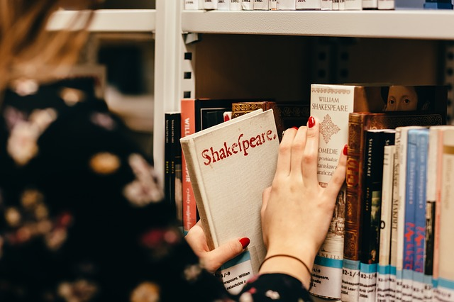 A woman access a book of Shakespeare from a library shelf.