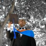 A graduate wears a gown and holds a mortar board with tassel among a tree-filled background.