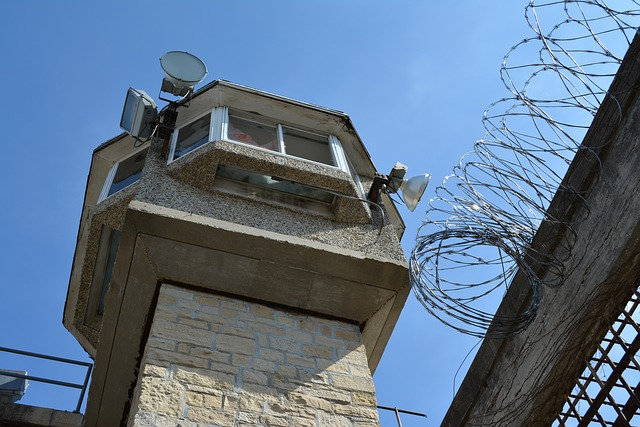 A prison guard tower above a barbed wire fence.