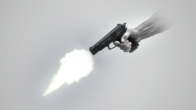 A handgun being fired with a plume of fire extending from the barrel and into the air.