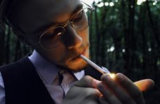 A man lights a cigarette outdoors.l