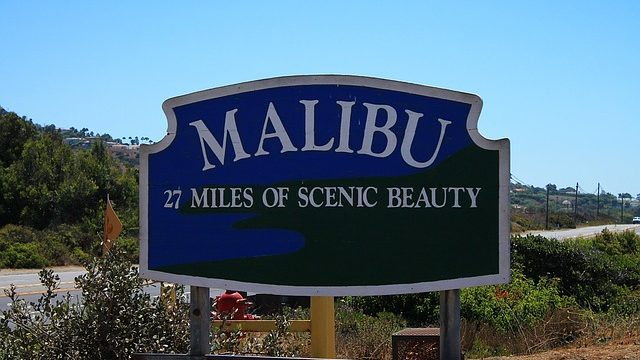 "A sign reading, ""Malibu, 27 Miles of Scenic Beauty."""