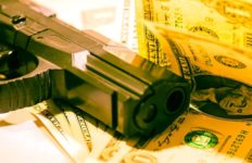 A gun lays on top of several dollar bills.