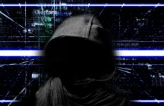 A computer hacker with face masked by darkness wears a hooded shirt with lines of computer code illuminated in the background.