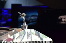 A close-up of the hood ornament of a Rolls-Royce vehicle, similar to the kinds of vehicles used by royalty.